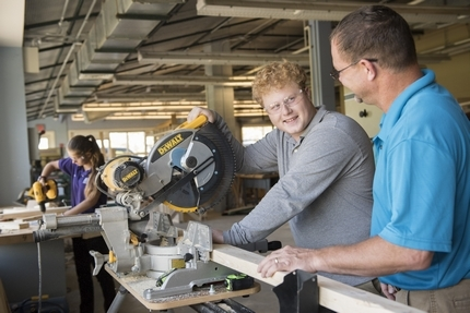 red haired high school student wearing safety glasses cuts wood on a rotating saw. Teacher in blue shirt looks on.